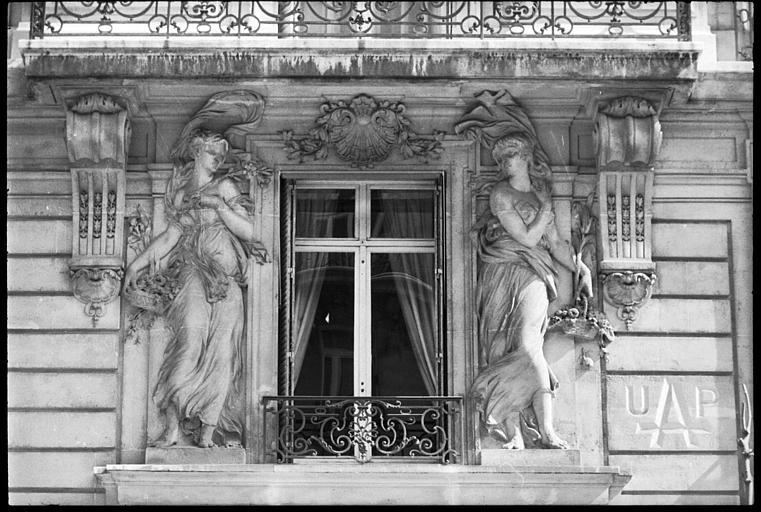 Façade ornée de deux statues féminines monumentales : vue rapprochée