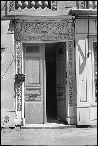 Porte ornée de rinceaux sculptés et de deux têtes
