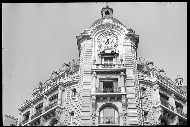 Angle de deux façades : horloge soutenue par deux atlantes en pied
