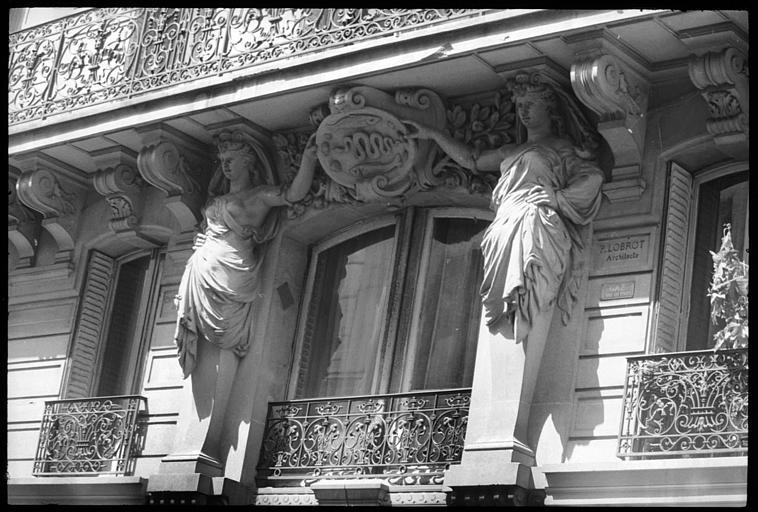 Façade ornée de deux cariatides en pied présentant un plat décoré dans le style des céramiques de Bernard Palissy : vue rapprochée