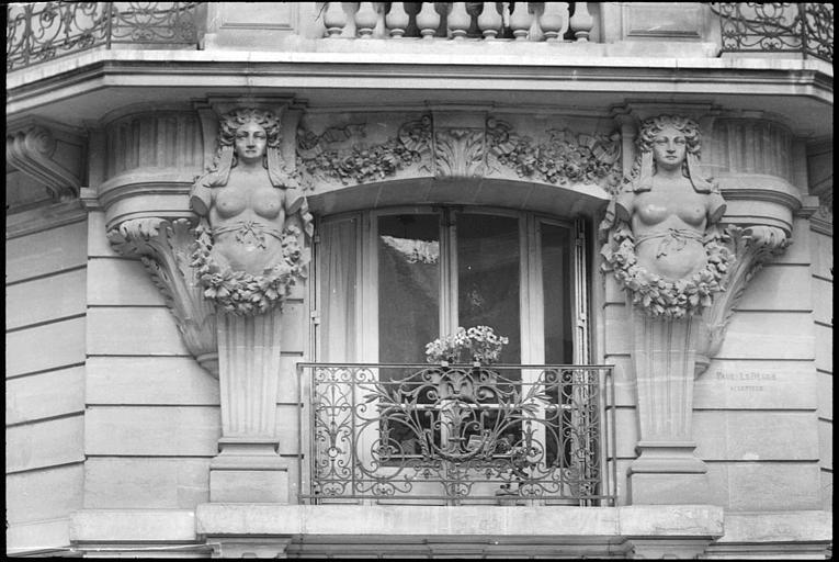 Angle de deux façades orné de deux cariatides en gaine sans bras : vue rapprochée