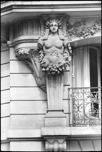 Angle de deux façades orné de deux cariatides en gaine sans bras : vue rapprochée de la cariatide de gauche