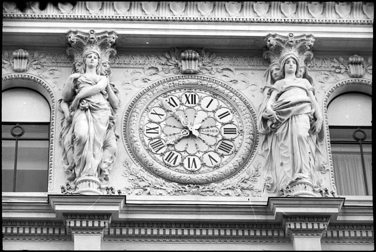 Triples cariatides en pied supportant un fronton : vue rapprochée des cariatides de part et d'autre de l'horloge