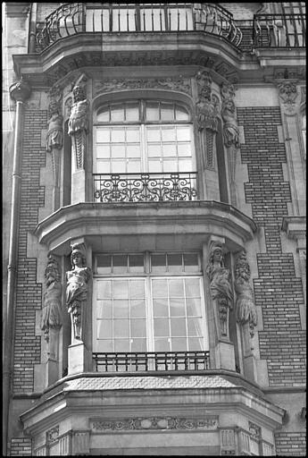 Façade avec bow-windows ornés d'atlantes et de cariatides en gaine sans bras : vue rapprochée des bow-windows
