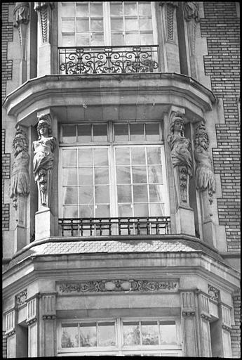 Façade avec bow-windows ornés d'atlantes et de cariatides en gaine sans bras : vue rapprochée d'un bow-window