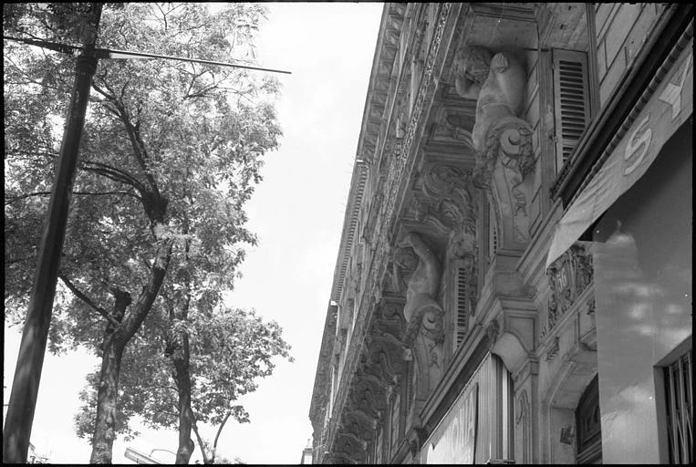 Façade ornée de deux atlantes en gaine avec bras : vue diagonale en contreplongée