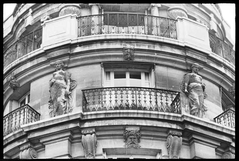 Angle de deux façades orné de deux cariatides en pied : vue rapprochée