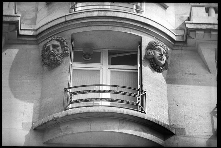Partie de la façade ornée d'une tête d'atlante et d'une tête de cariatide : vue rapprochée