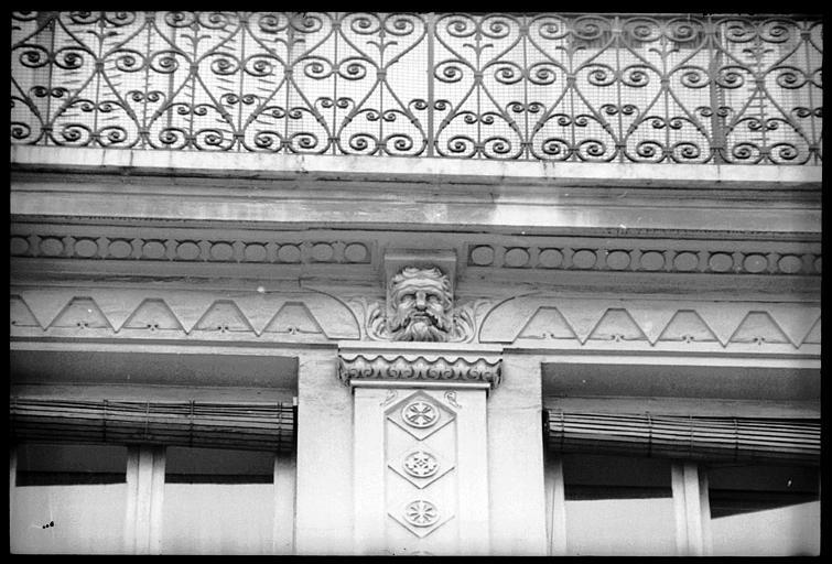 Façade ornée de têtes d'atlantes : vue rapprochée d'une tête
