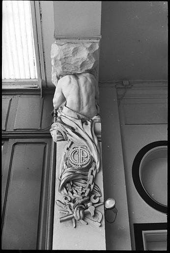 Entrée ornée d'atlantes en gaine avec bras : vue rapprochée d'un atlante