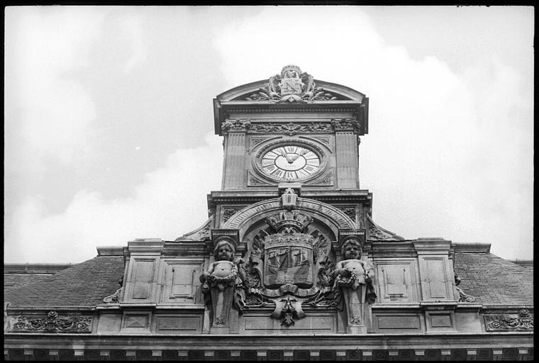 Partie supérieure de la façade : horloge et écusson flanqué de deux enfants atlantes  en gaine avec bras