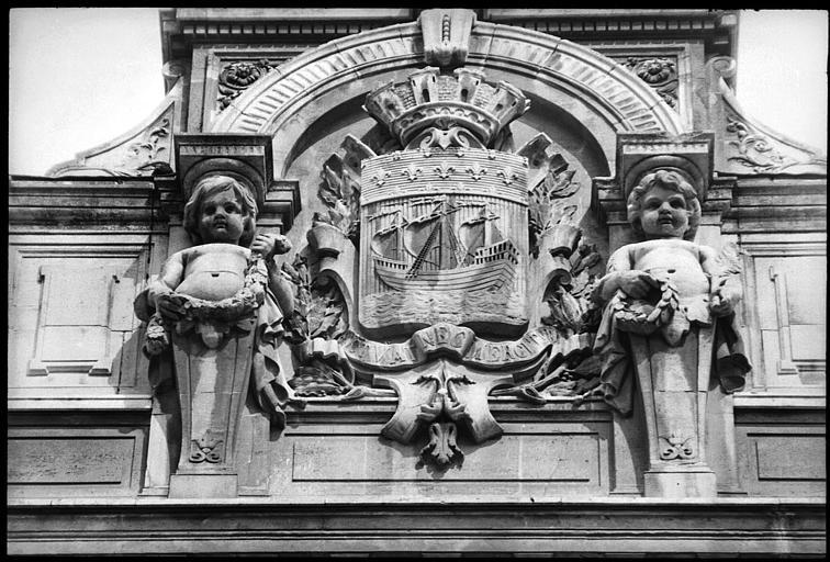 Partie supérieure de la façade : écusson flanqué de deux enfants atlantes en gaine avec bras