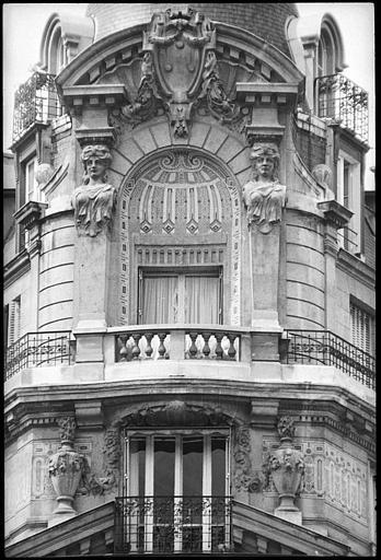 Angle de deux façades orné d'une niche décorée de mosaïques et flanquée de deux bustes de cariatides : vue rapprochée