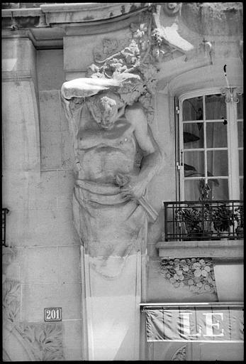 Façade ornée d'atlantes en gaine avec bras : vue rapprochée d'un atlante
