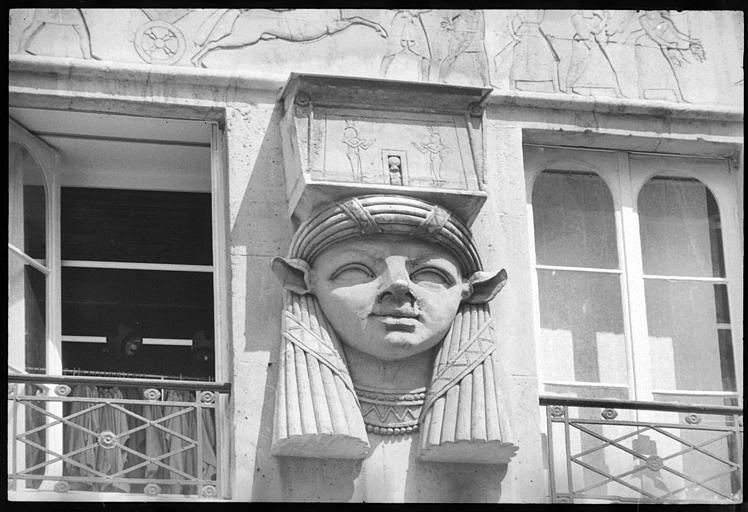 Façade ornée de trois têtes cariatides de style égyptien : vue rapprochée d'une tête