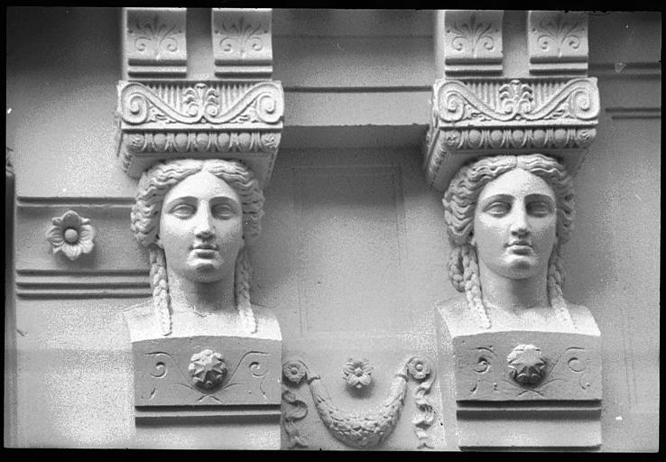 Façade ornée de quatre cariatides en buste : vue rapprochée des deux cariatides de droite