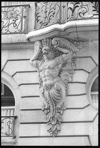 Façade ornée de deux atlantes en gaine en forme de créature fantastique : vue rapprochée de l'atlante de gauche