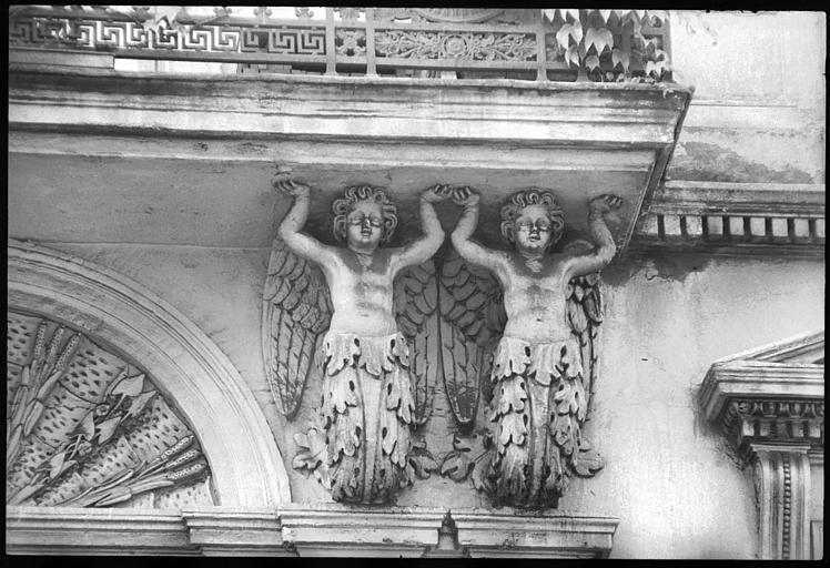 Façade ornée de deux paires d'atlantes ailés en gaine avec bras : vue rapprochée des atlantes de droite