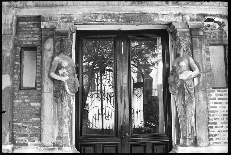 Porte d'entrée flanquée de deux cariatides en gaine avec bras
