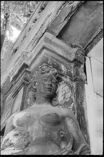 Porte d'entrée flanquée de deux cariatides en gaine avec bras : buste de la cariatide de gauche
