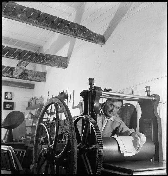 [Portrait de Henri-Georges Adam dans son atelier appuyé sur une presse à graver]