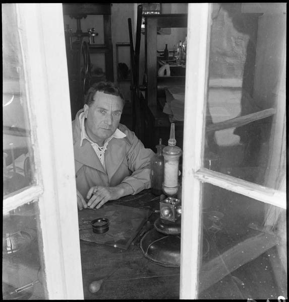 [Portrait de Henri-Georges Adam dans son atelier gravant assis à son bureau]