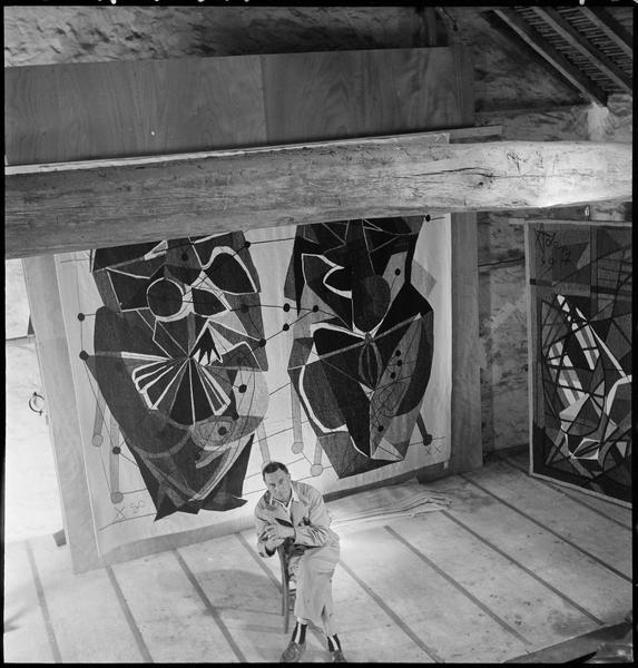 [Portrait en plongée de Henri-Georges Adam assis dans son atelier devant ses cartons de tapisserie (grands formats)]