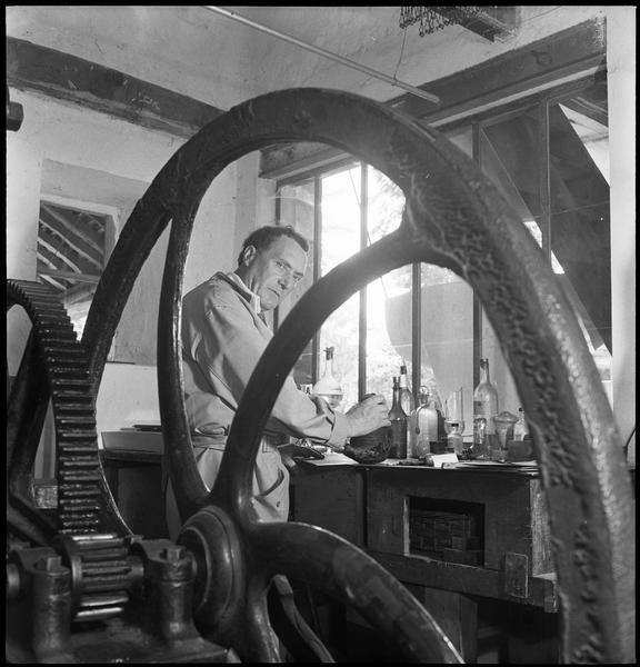 [Portrait de Henri-Georges Adam dans son atelier préparant une plaque derrière une presse à graver]