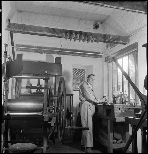 [Portrait de Henri-Georges Adam dans son atelier préparant une plaque à côté d'une presse à graver]
