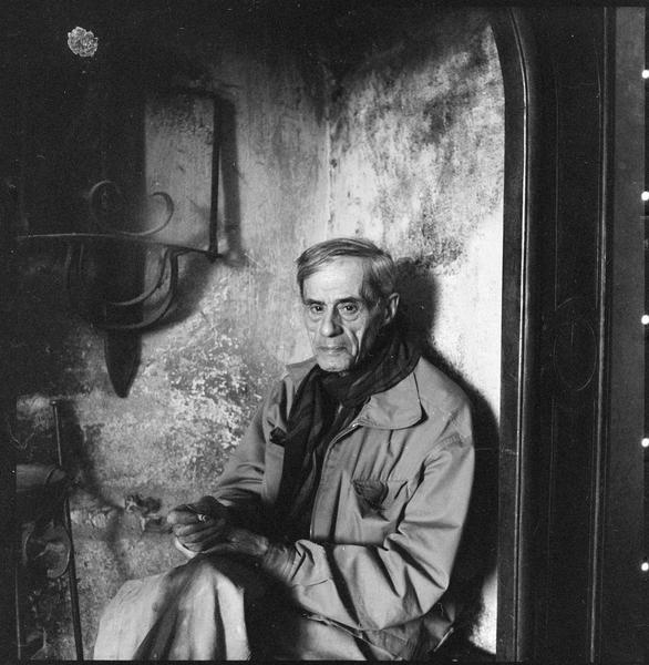[Portrait de Roger Bissière assis sur un banc sous une grande cheminée]