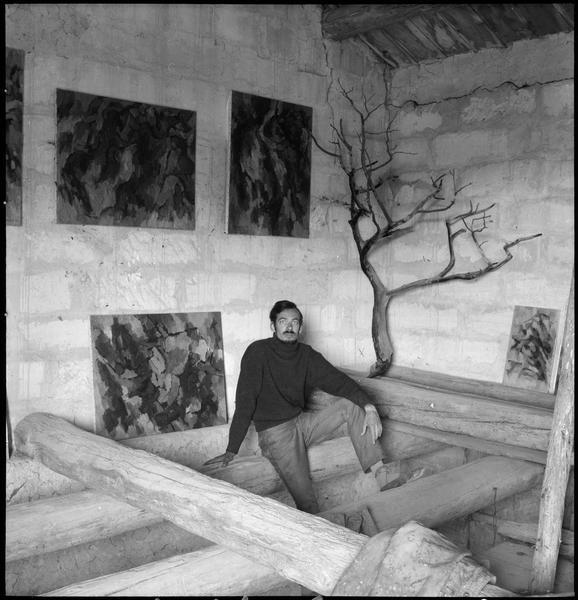 [Portrait de Gérard Cabus assis dans l'atelier au milieu de ses oeuvres]