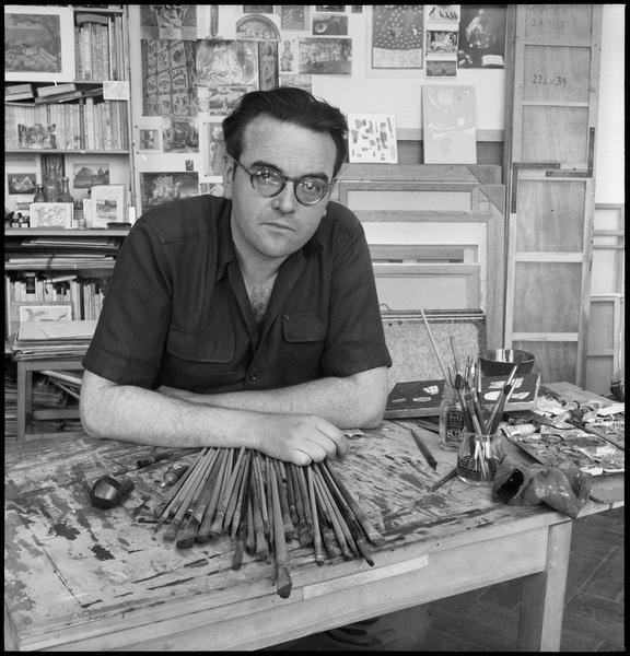 [Portrait de Sergio de Castro dans son atelier assis derrière une table de travail]