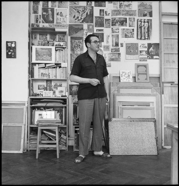 [Portrait de Sergio de Castro dans son atelier devant un mur d'images diverses]