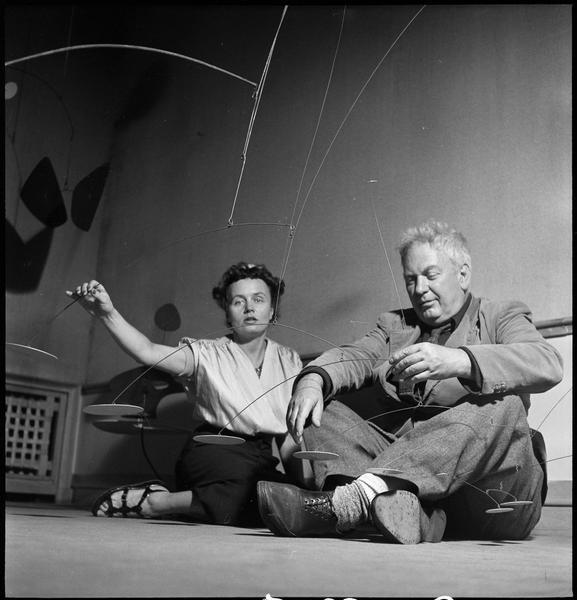 [Exposition Alexander Calder, juillet 1950 : Alexander Calder et Andrée Vilar assis à côté d'un mobile]