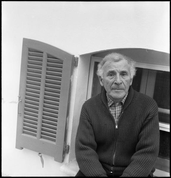 [Portrait de Marc Chagall assis sur un appui de fenêtre devant sa maison]