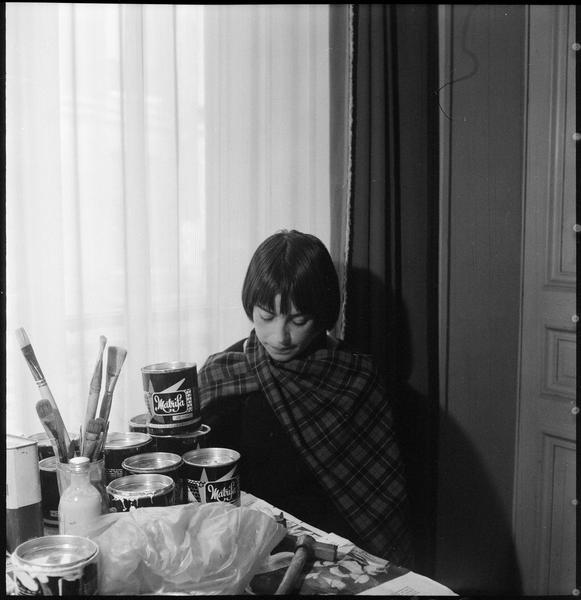 [Portrait de Lourdès Castro assise dans son atelier derrière sa table de travail]