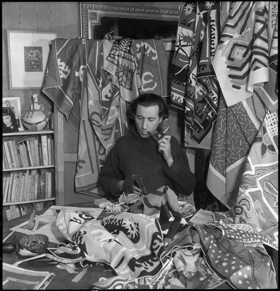 [Portrait de Marc Cavell assis dans son atelier au milieu de ses créations textiles]