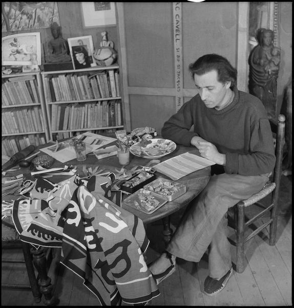 [Portrait de Marc Cavell assis dans son atelier à sa table de travail devant une création textile]