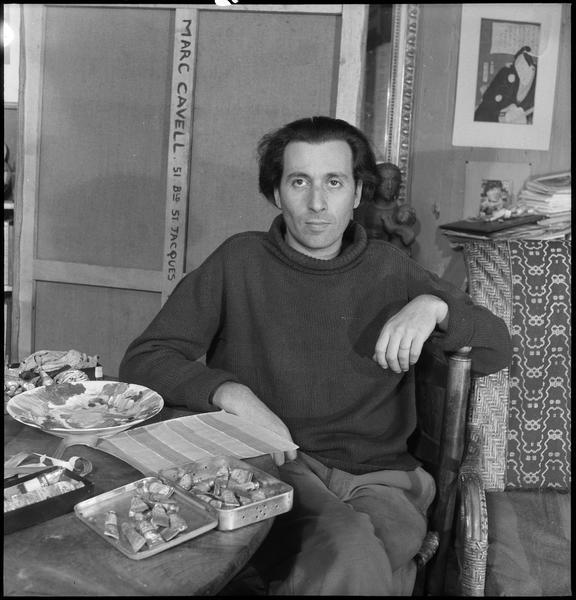[Portrait de Marc Cavell assis dans son atelier à sa table de travail]