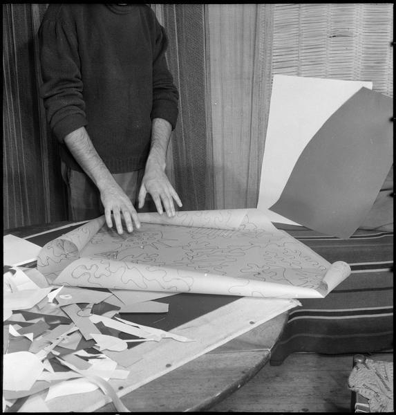 [Marc Cavell dans son atelier montrant un calque pour une création textile]