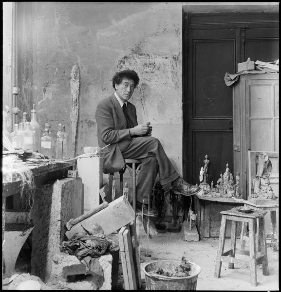 [Portrait d'Alberto Giacometti assis dans son atelier au milieu de ses oeuvres, une petite tête modelée dans les mains]