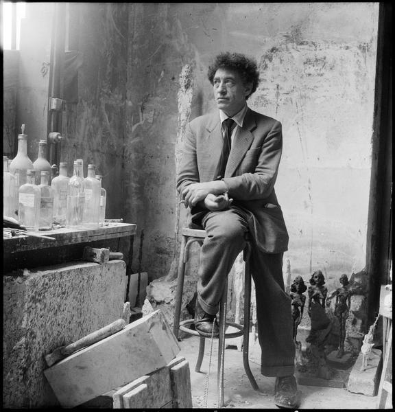 [Portrait d'Alberto Giacometti assis dans son atelier au milieu de ses oeuvres]