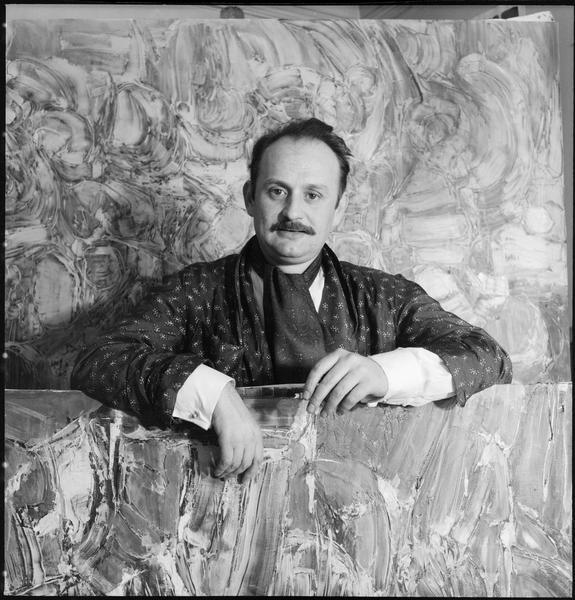 [Portrait de Roger-Edgar Gillet dans son atelier au milieu de ses oeuvres]