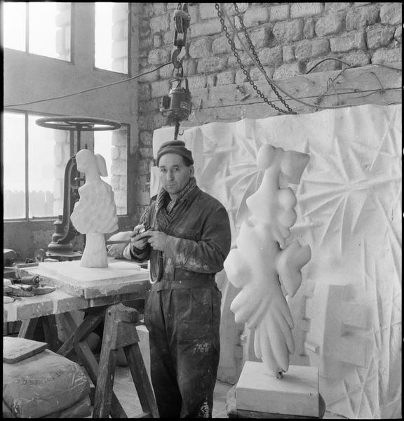 [Portrait d'Etienne Hajdu dans son atelier au milieu de ses oeuvres, préparant une fraiseuse]