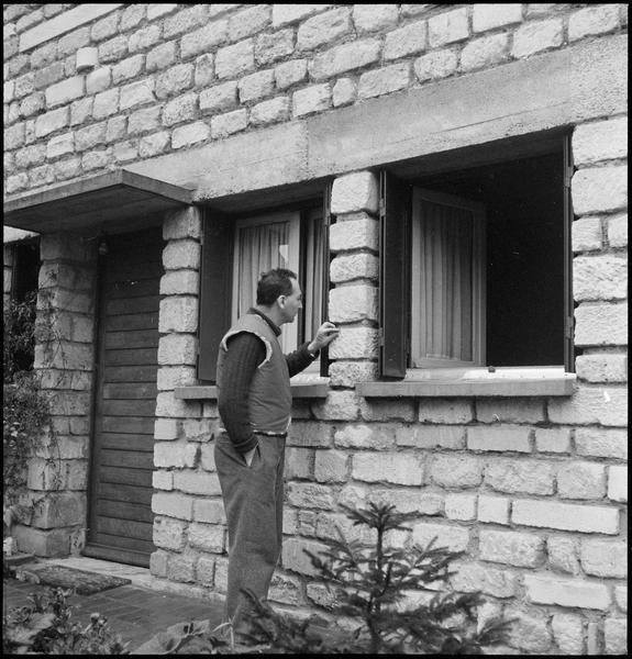 [Portrait d'Etienne Hajdu touchant les pierres taillées de la façade de son atelier-maison]