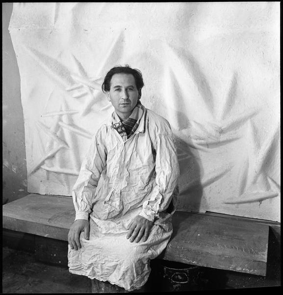 [Portrait d'Etienne Hajdu assis dans son atelier devant un bas-relief]