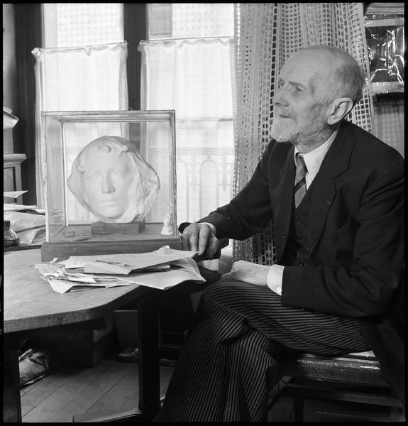 [Portrait de Henri Hamm assis à côté d'une tête sculptée]