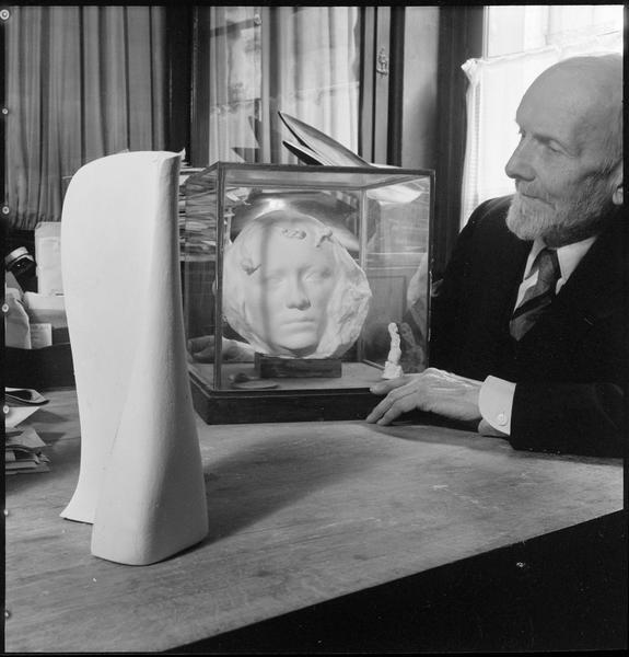 [Portrait de Henri Hamm assis à côté de ses oeuvres]