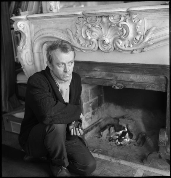 [Portrait de Simon Hantaï accroupi devant la cheminée]