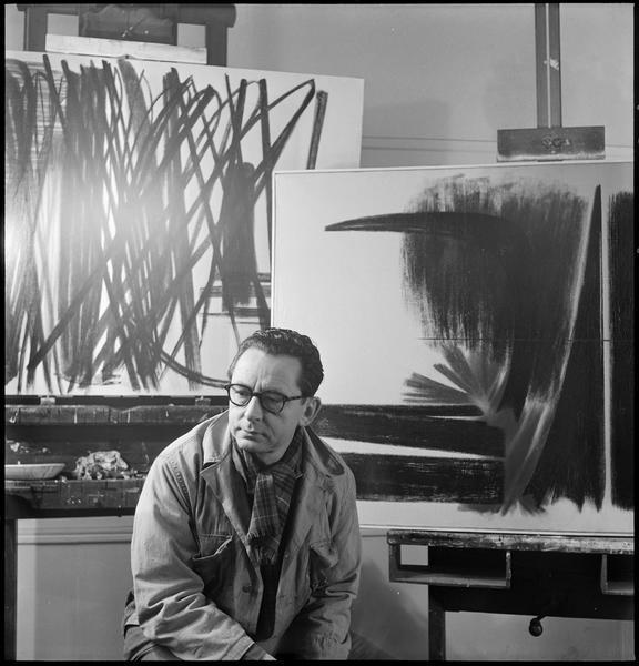 [Portrait de Hans Hartung assis dans son atelier devant ses oeuvres]